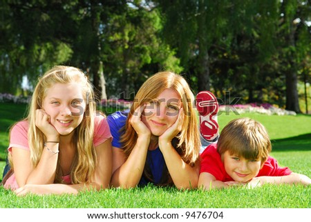 Portrait of a family - mother and children - relaxing in summer park - stock photo