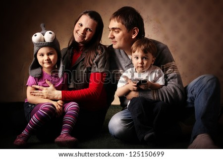 portrait of a family of four, mom dad daughter and son, with young children