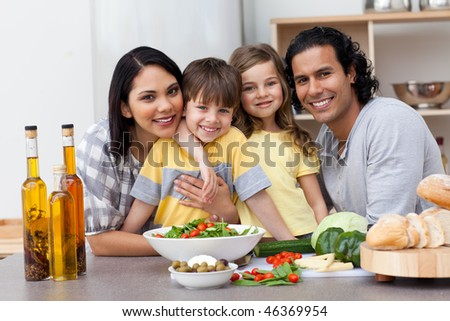 Portrait of a family posing in the kitchen - stock photo