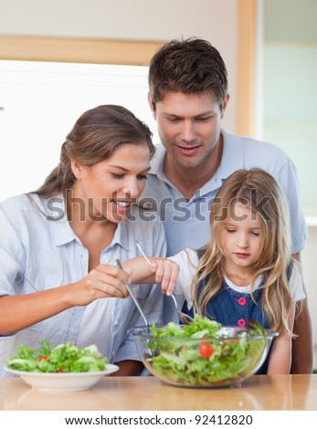 Portrait of a family preparing a salad in their kitchen - stock photo