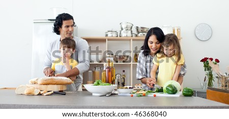 Portrait of a family preparing lunch in the kitchen - stock photo