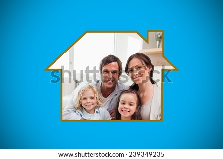 Portrait of a family relaxing in their living room against blue background with vignette - stock photo
