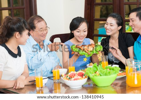 Portrait of a family tasting delicious chicken together - stock photo