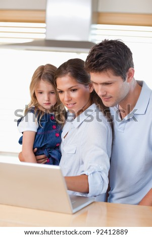 Portrait of a family using a laptop in their kitchen - stock photo