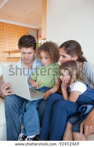 Portrait of a family using a notebook in their living room - stock photo