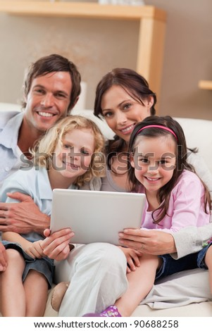 Portrait of a family using a tablet computer in a living room - stock photo