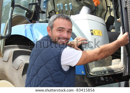 portrait of a farmer climbing on tractor - stock photo