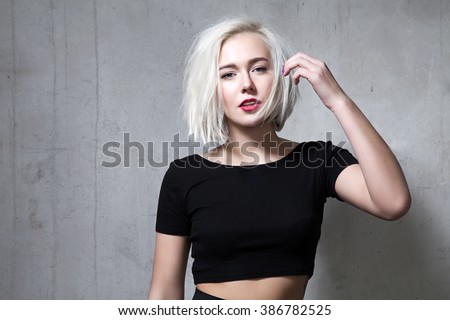 Portrait of a fashion blonde with short hair and wearing a black T-shirt on the background of a cement wall - stock photo
