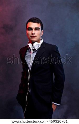 Portrait of a fashion guy listening music with headphones. Studio shot. Dark background. Smoke. - stock photo