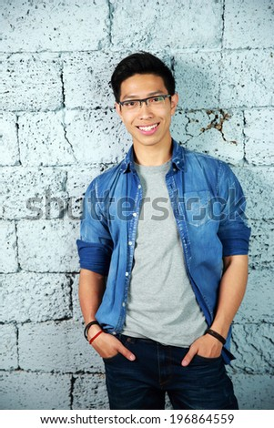 Portrait of a fashion happy asian man leaning on brick wall - stock photo