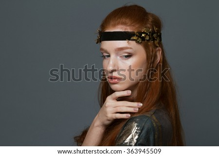 Portrait of a fashion redhead woman posing over gray background - stock photo