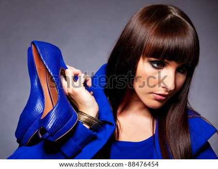 Portrait of a fashion woman holding elegant shoes - stock photo