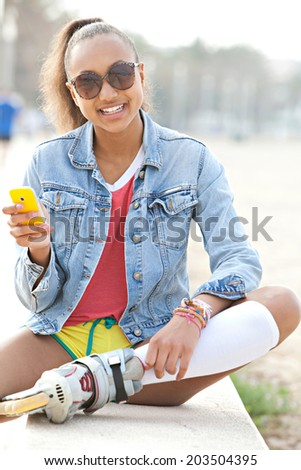 Portrait of a fashionable african american teenager girl sitting on the wall of a beach in a destination city using a smartphone while roller skating. Recreational technology lifestyle, outdoors. - stock photo