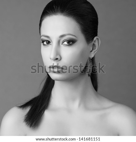 Portrait of a fashionable brunette with long hair in trendy vintage earrings and great make-up posing over gray background. black and white (monochrome) studio shot