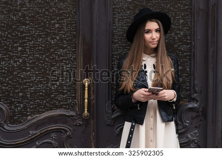 Portrait of a fashionable brunette woman with cool look holding mobile phone while standing on the street against wooden door, young charming female with beautiful long hair posing with cell telephone - stock photo