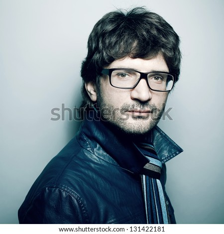 Portrait of a fashionable handsome man in blue jacket with striped scarf posing over light blue background. Hipster style. Perfect hair. Close-up. Studio shot - stock photo