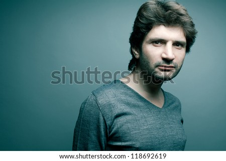 Portrait of a fashionable handsome man in gray sweater (pullover) over blue (green) background. Copy-space. studio shot