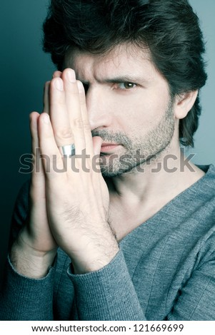 Portrait of a fashionable handsome man in gray sweater (pullover) praying over dark blue (green) background. Studio shot - stock photo