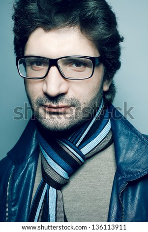 Portrait of a fashionable handsome man in trendy glasses, blue jacket with striped scarf posing over light blue background. Hipster style. Close up. Studio shot - stock photo