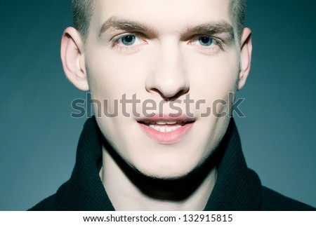 Portrait of a fashionable handsome man posing over dark blue background. Vogue style. Close up. Studio shot. - stock photo