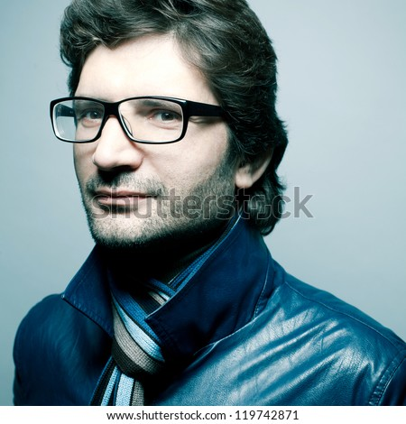 Portrait of a fashionable handsome man with a friendly smile in blue jacket with striped scarf over light blue background. Close-up. studio shot - stock photo