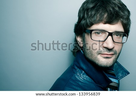 Portrait of a fashionable handsome mature man in blue jacket with striped scarf posing over light blue background. Close-up. Copy-space. Studio shot - stock photo