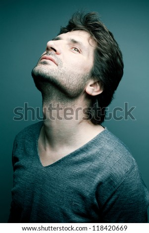 Portrait of a fashionable handsome model in gray sweater (pullover) over blue (green) background with his chin up. Close-up. studio shot - stock photo