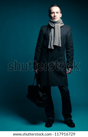 Portrait of a fashionable male model over dark blue background. studio shot