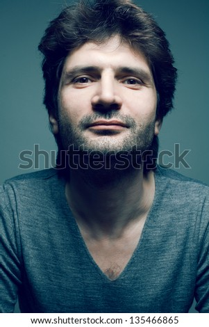 Portrait of a fashionable mature handsome man in gray sweater (pullover) posing over dark blue (green) background with a friendly smile. Close up. Studio shot - stock photo