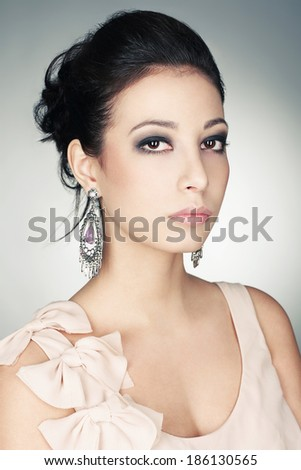 Portrait of a fashionable model with perfect skin an make-up posing over gray background. Vintage earrings and great hairdo. Pink retro dress with bow-knots & decollete. Close up. Studio shot - stock photo