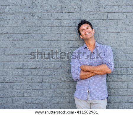 Portrait of a fashionable older man laughing against gray background - stock photo