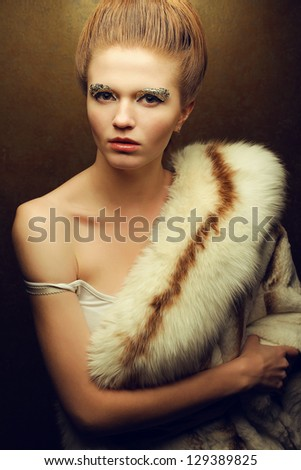 Portrait of a fashionable red-haired (ginger) model with perfect arty make-up wearing luxury fur coat and posing over golden background. Studio shot - stock photo