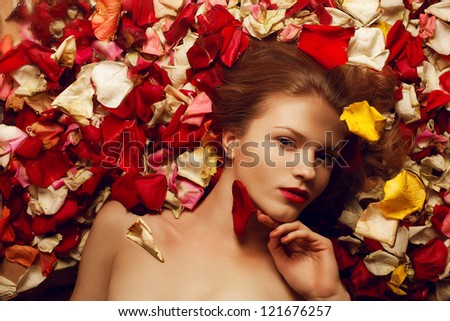 Portrait of a fashionable red-haired (ginger) model with sexy red lips lying on rose petals background and holding red petal. Studio shot