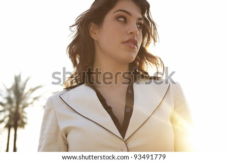 Portrait of a fashionable woman with sun rays filtering from the back. - stock photo