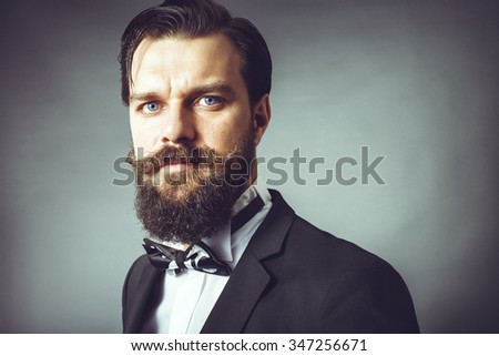 Portrait of a fashionable young man with retro look. Studio shot - stock photo