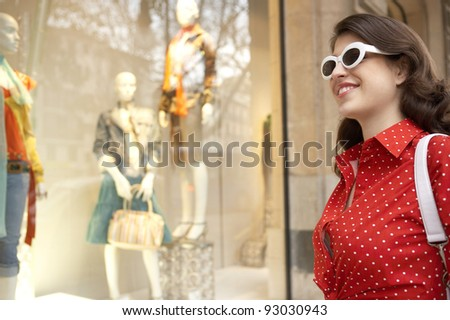 Portrait of a fashionable young woman looking at a shop window. - stock photo