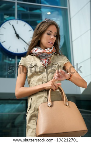 Portrait of a fashionable young woman looking at watch outdoors - stock photo