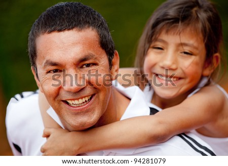 Portrait of a father and daughter at the tennis court smiling - stock photo