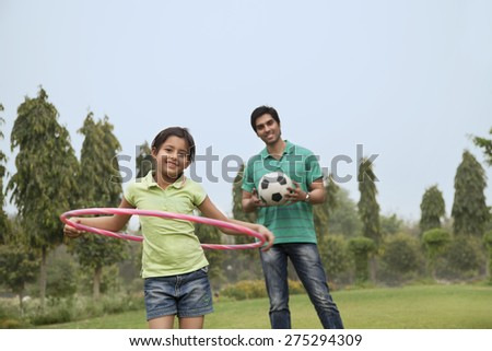 Portrait of a father and his daughter playing outdoors - stock photo