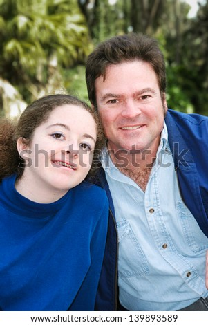 Portrait of a father and his teenage daughter posing outdoors.