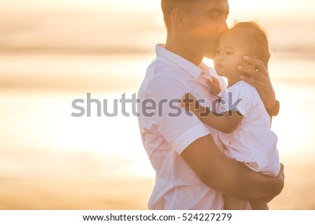 portrait of a Father and little baby daughter on beach at sunset