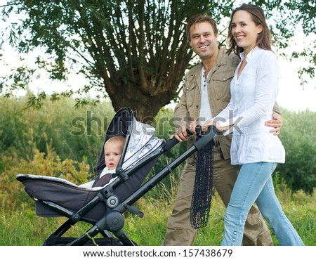 Portrait of a father and mother smiling outdoors and walking baby in pram - stock photo