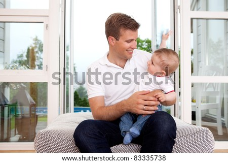 Portrait of a father and son smiling, looking at each other in a home interior - stock photo