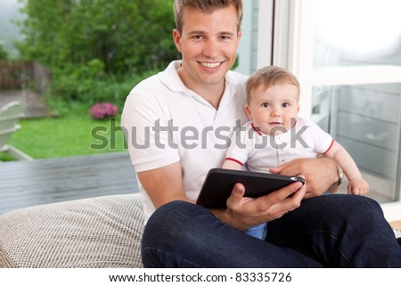 Portrait of a father and son with a digital tablet in a home interior - stock photo