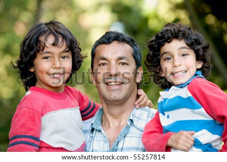 Portrait of a father carrying his sons outdoors and smiling - stock photo