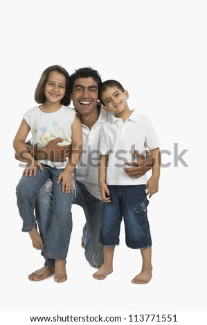 Portrait of a father hugging his children