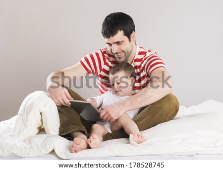 Portrait of a father with his son in bed - stock photo
