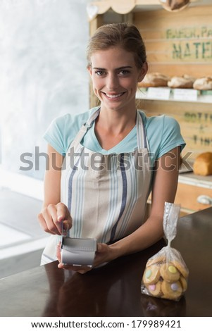 Portrait of a female barista using credit card at the counter in coffee shop - stock photo
