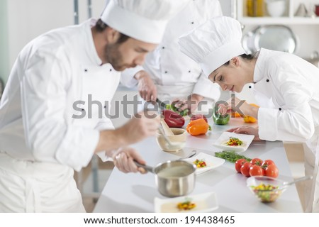 Portrait of a female chef preparing a dish carefully - stock photo