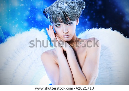 Portrait of a female christmas angel over sky of stars and snow. - stock photo